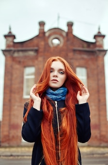 Woman with long red hair walks in autumn on the street