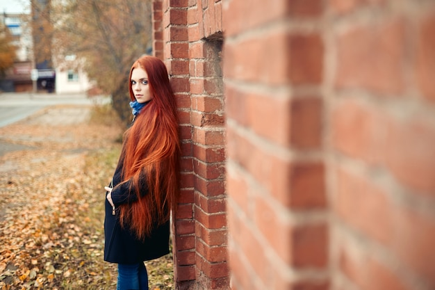 Woman with long red hair walks in autumn