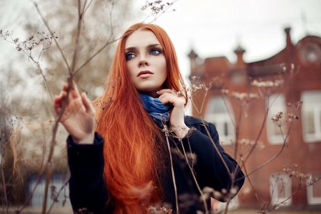 赤い長い髪の女性は、秋に路上を歩きます。ミステリアスなドリーミーな表情と女の子のイメージ。歩く赤毛の女性