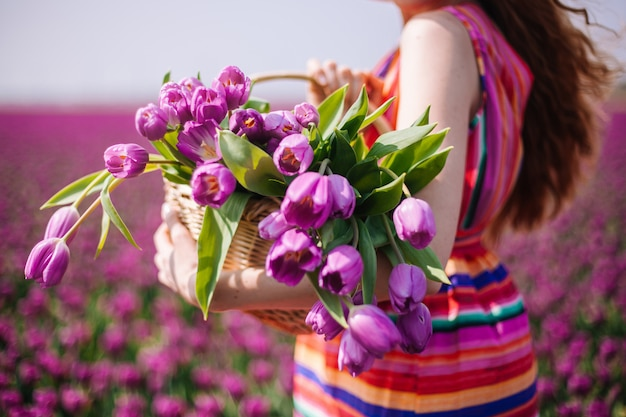 Woman with long red hair wearing a striped dress holding a basket with bouquet of purple tulips flowers