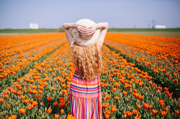 Woman with long red hair wearing a striped dress  standing by the back on colorful tulip field.