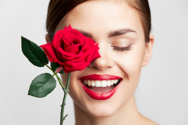 Woman with long smile closed eyes rose near the face hair clear skin light background