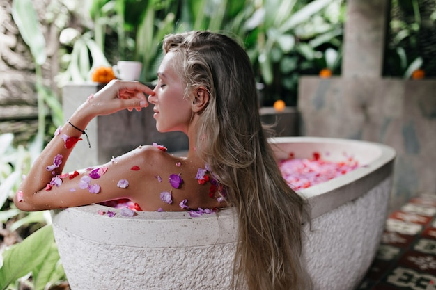 Woman with long straight hair sitting in bath full of rose petals. indoor shot of magnificent tanned woman resting at home and doing spa.