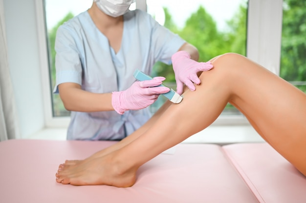 Woman with long tanned perfect legs and smooth skin having wax stripe depilation