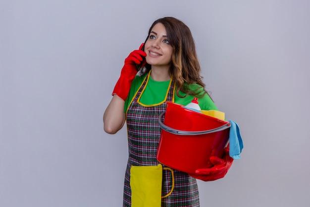 Donna con lunghi capelli ondulati in grembiule e guanti che tiene secchio con strumenti di pulizia mentre parla al telefono cellulare sorridente in piedi