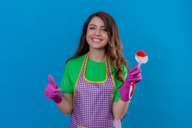 Donna con lunghi capelli ondulati in grembiule e guanti tenendo la spazzola per strofinare sorridendo allegramente mostrando il pollice in piedi sul blu