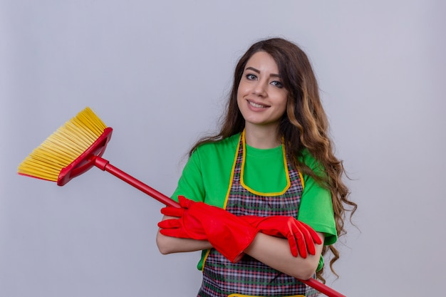 Woman with long wavy hair in apron and gloves standing with arms crossed with mop