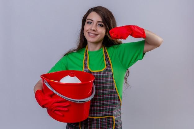 エプロンと手袋を保持しているバケツを保持している手袋で長いウェーブのかかった髪を持つ女性