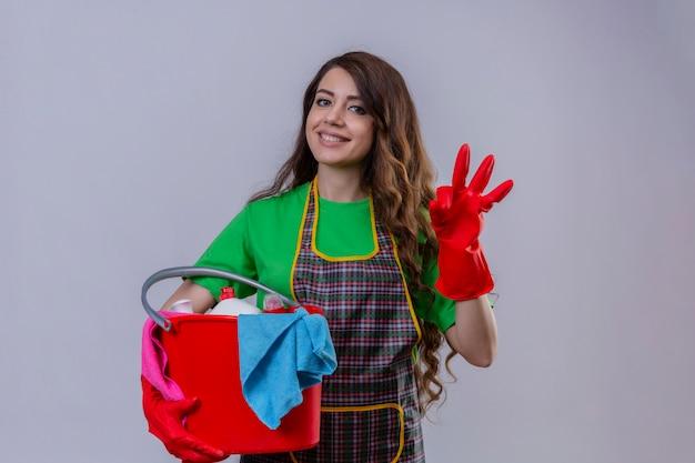 エプロンと手袋を保持している手袋でバケツを保持しているokの標識を示すフレンドリーな立っている笑顔のクリーニングで長いウェーブのかかった髪を持つ女性