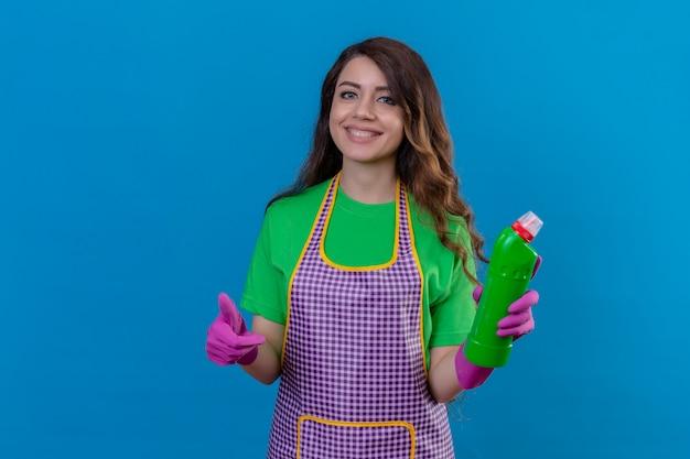 エプロンと手袋を保持しているクリーニングの供給を保持している手袋の長いウェーブのかかった髪を持つ女性