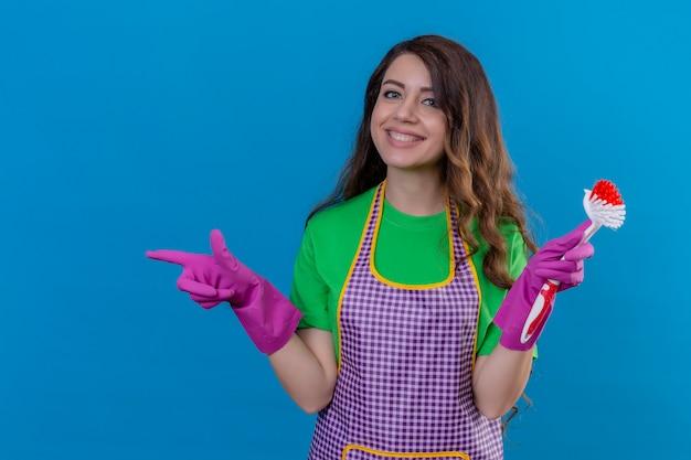 エプロンと手袋で元気に青の上に立って笑顔側を指しているスクラブブラシを保持している手袋で長いウェーブのかかった髪を持つ女性