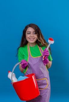 長いウェーブのかかった髪のエプロンとゴム手袋を着用してバケツを掃除用品とスクラブブラシで青に優しい立っている笑顔を着て