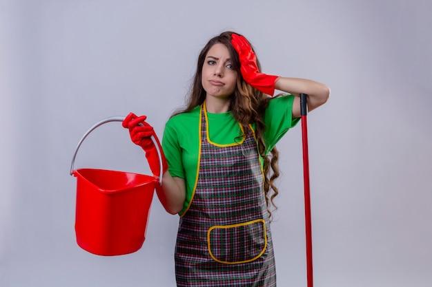 Женщина с длинными волнистыми волосами в фартуке и резиновых перчатках держит пустое ведро, касается головы, выглядит грустной, уставшей от уборки