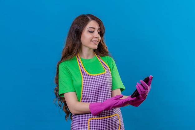 青の上に立っている顔に笑顔で画面を見ている手で携帯電話を保持しているエプロンとゴム手袋を着用して長いウェーブのかかった髪を持つ女性
