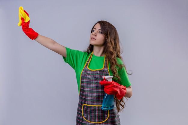 長いウェーブのかかった髪のエプロンと敷物を保持しているゴム手袋をはめて、スプレーのスプレーを脇に立って自信を持って深刻な表情で立っている女性