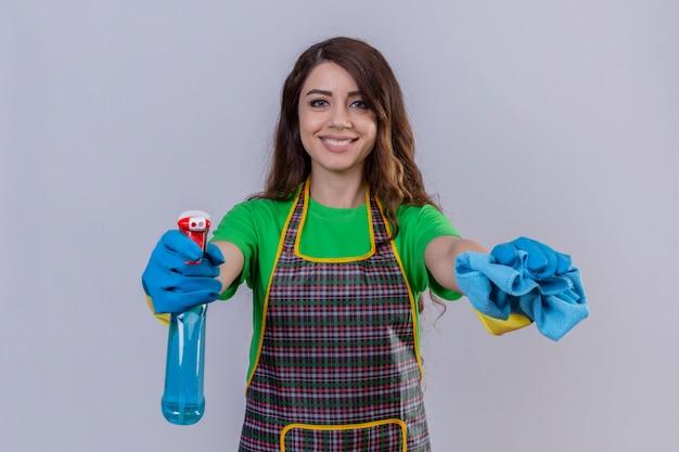 長いウェーブのかかった髪のエプロンと敷物を保持し、スプレーを洗浄しているゴム手袋をはめている女性