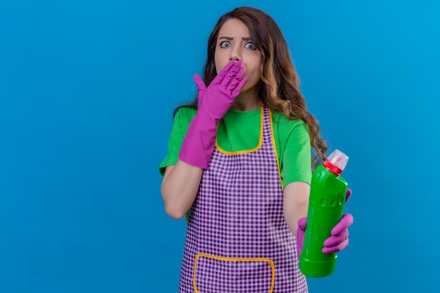青の上に立っている手円錐形の口で驚いたクリーニング用品のボトルを保持しているエプロンとゴム手袋を着用して長いウェーブのかかった髪を持つ女性