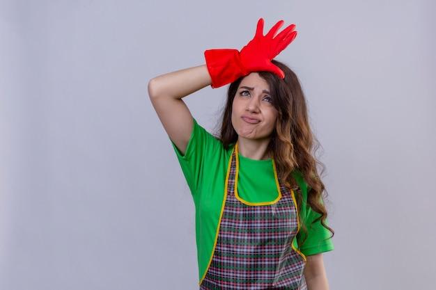 Женщина с длинными волнистыми волосами в фартуке и резиновых перчатках высмеивает людей с пальцами на лбу, делая жест неудачника стоя