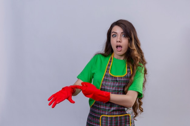 エプロンとゴム手袋をはめた長いウェーブのかかった髪の女性が顔を立って懐疑的な表情で時間について思い出させる彼女の手を指しています。