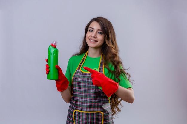 エプロンとゴム手袋をはめた長いウェーブのかかった髪を持つ女性は、フレンドリーな立ちを笑顔でボトルを指してボトルを指しています。