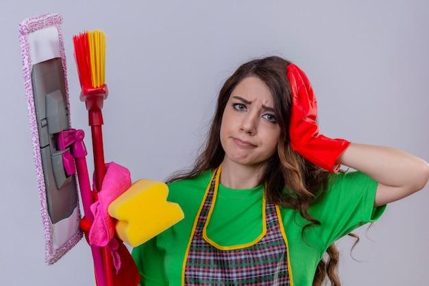Женщина с длинными волнистыми волосами в фартуке и резиновых перчатках, стоящая с чистящими средствами и швабрами, трогающая голову, грустная, уставшая от уборки