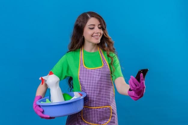 Donna con lunghi capelli ondulati che indossa un grembiule e guanti di gomma tenendo il bacino pieno di strumenti di pulizia guardando il telefono cellulare con il sorriso sulla faccia in piedi sul blu
