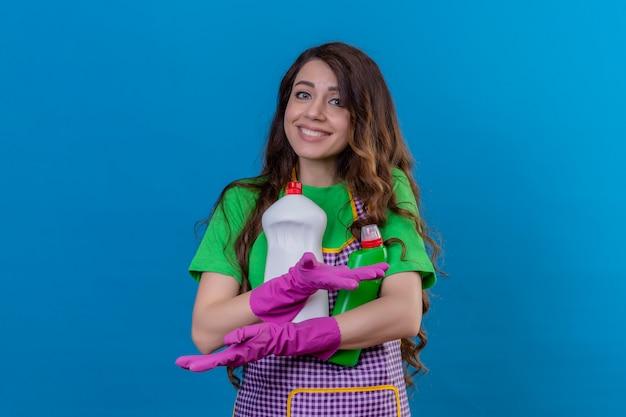 Donna con lunghi capelli ondulati che indossa grembiule e guanti di gomma che tiene bottiglie con prodotti per la pulizia sorridente in piedi amichevole sul blu