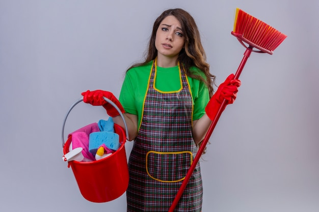 Woman with long wavy hair wearing apron and rubber gloves holding bucket with cleaning tools and mop looking sad and onworked with unhappy face standing