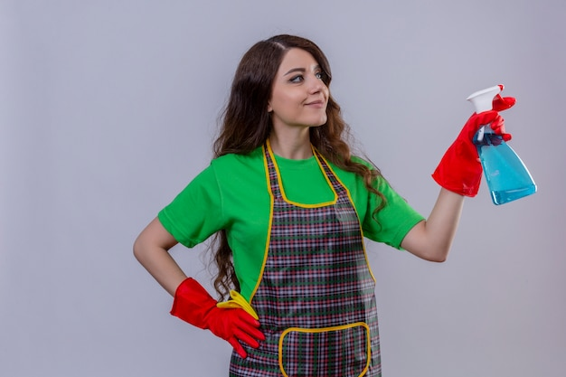 Woman with long wavy hair wearing apron and rubber gloves holding cleaning spray looking confident ready to clean standing