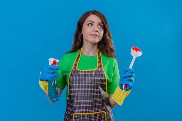 Donna con lunghi capelli ondulati che indossa un grembiule e guanti di gomma tenendo la spazzola per strofinare e spray per la pulizia cercando fiducioso pronto per pulire in piedi sul blu