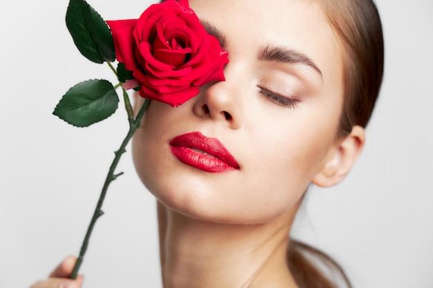 Женщина с длинными с закрытыми глазами держит прическу розового лица с чистой кожей крупным планом Premium Фотографии