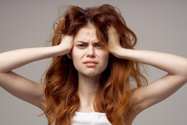 緩い髪の女性は手で彼女の頭に触れます白いtシャツ灰色の背景