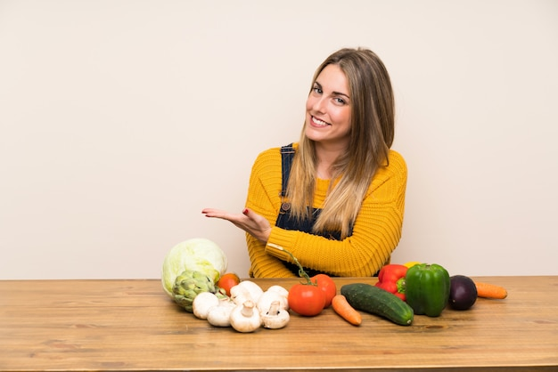 Woman with lots of vegetables extending hands to the side for inviting to come