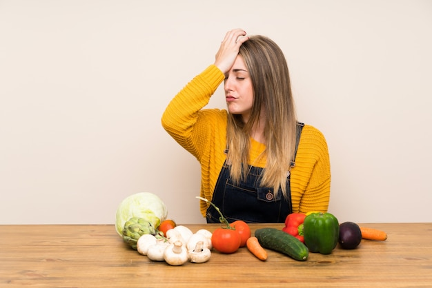 Woman with lots of vegetables having doubts with confuse face expression