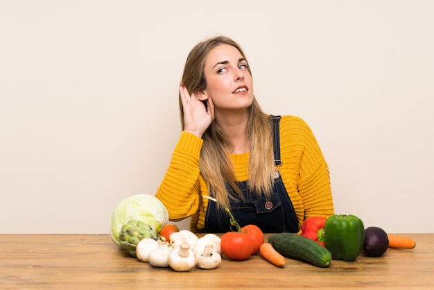 Woman with lots of vegetables listening something