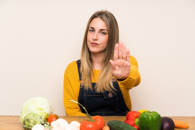 Woman with lots of vegetables making stop gesture with her hand