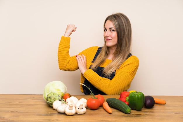 Woman with lots of vegetables making strong gesture