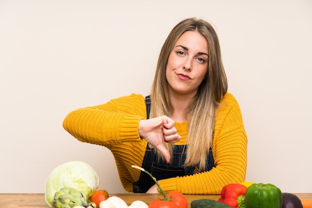 Woman with lots of vegetables showing thumb down sign