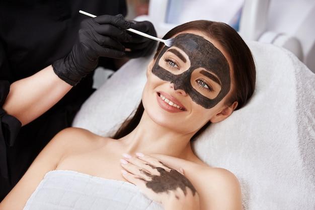 Женщина с прекрасной улыбкой, получающая уход за лицом с угольной маской косметологом в спа, клиентка салона красоты, имеющая процедуры для лица