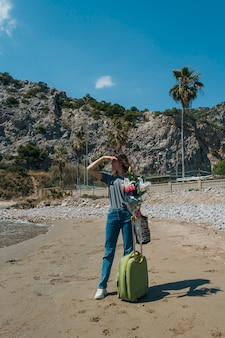 Woman with luggage bag and flower bouquet shielding her eye standing on beach