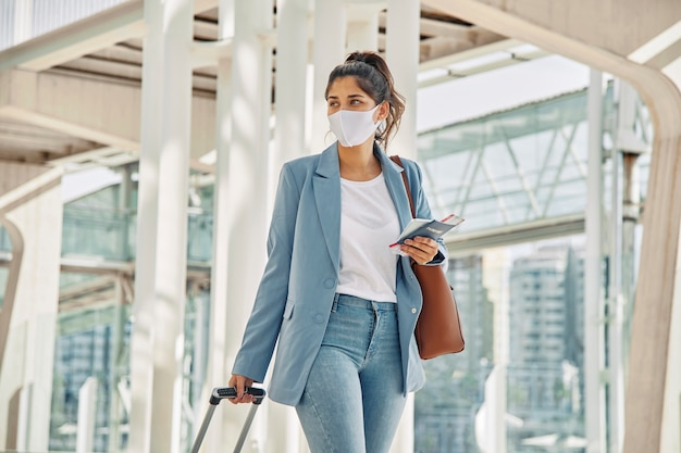 Woman with luggage and medical mask at the airport during pandemic