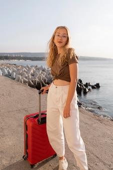 Donna con bagagli in posa oudoors