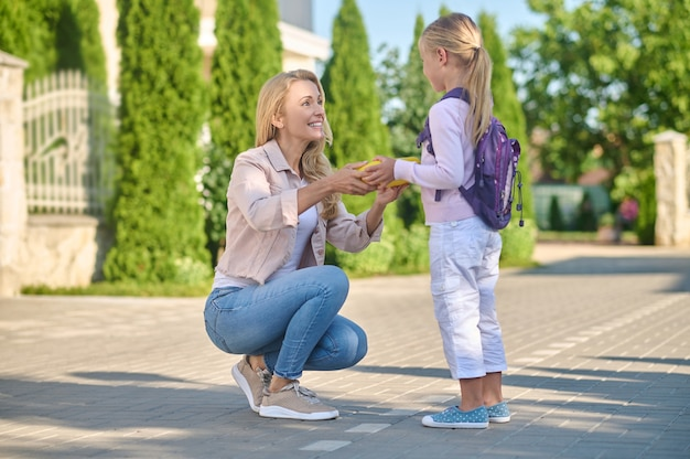Woman with lunchbox crouched next to little daughter