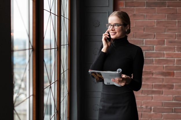 電話で話している雑誌を持つ女性