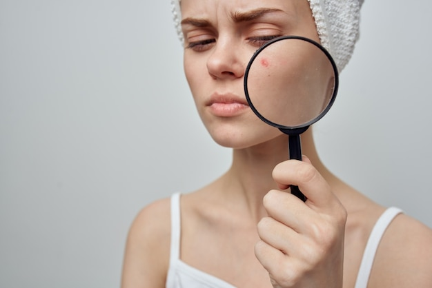 Woman with a magnifying glass in hand cosmetology studio. high quality photo