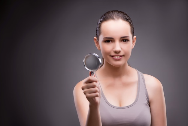 Woman with magnifying glass in sports concept