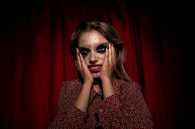 Donna con make-up di sangue sul viso tenendo la testa