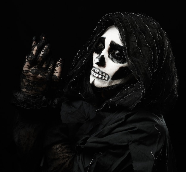 Woman with a make-up skeleton stands in black clothes and a transparent hood