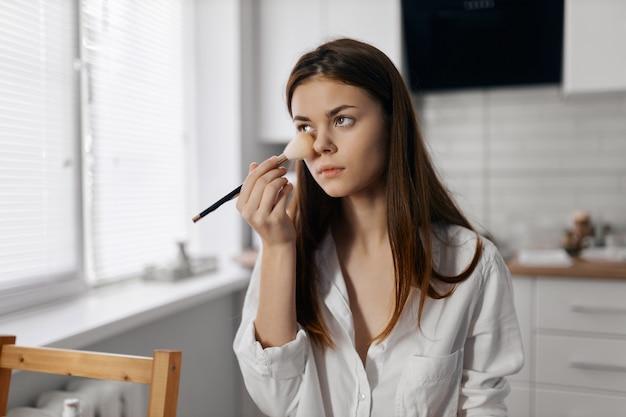 顔に化粧ブラシファンデーションを持つ女性