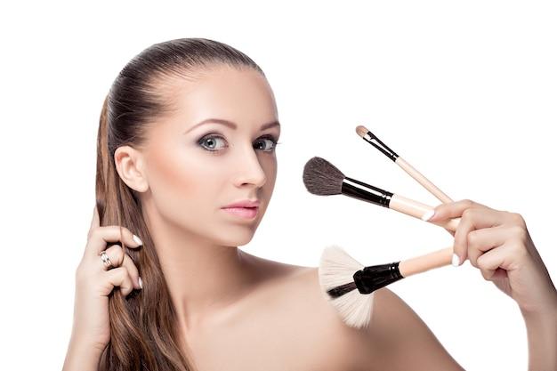 Женщина с кистями для макияжа